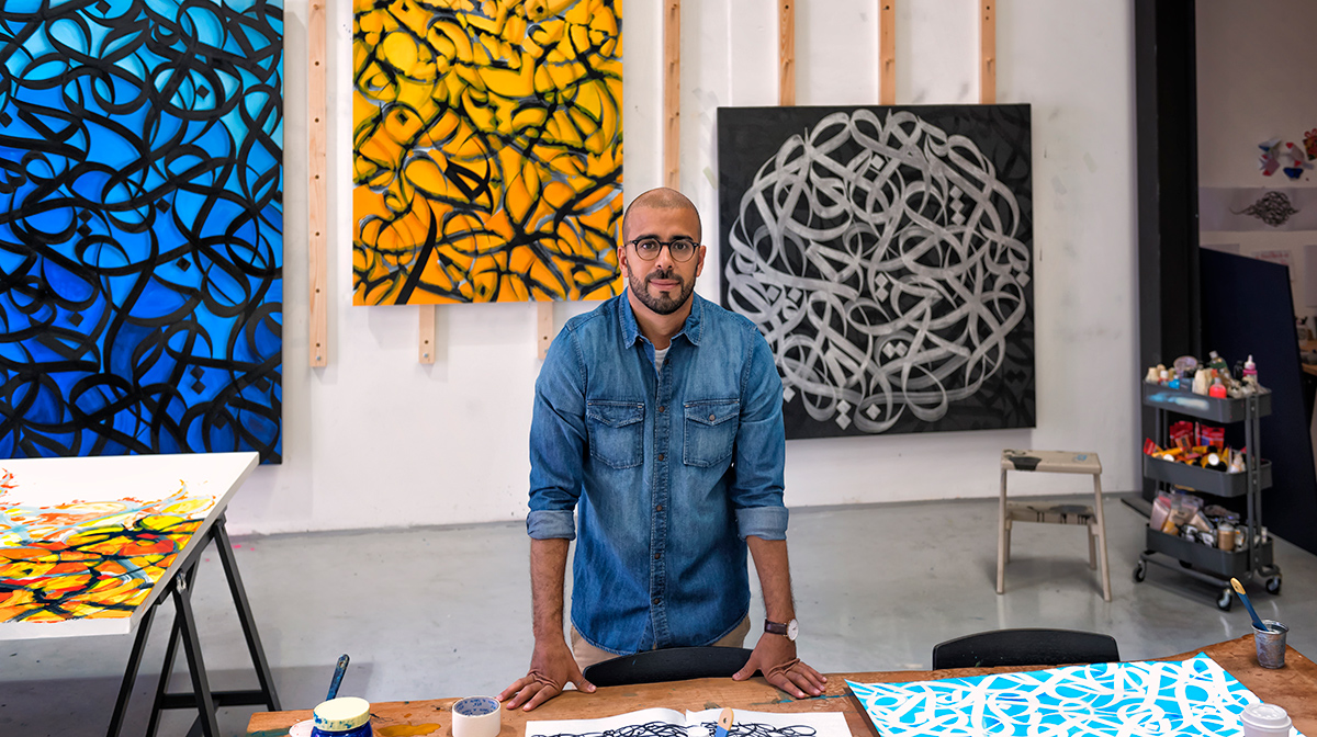 eL Seed stands in front of several of his colourful, and abstract artworks that are hung on a wall, and behind a workbench