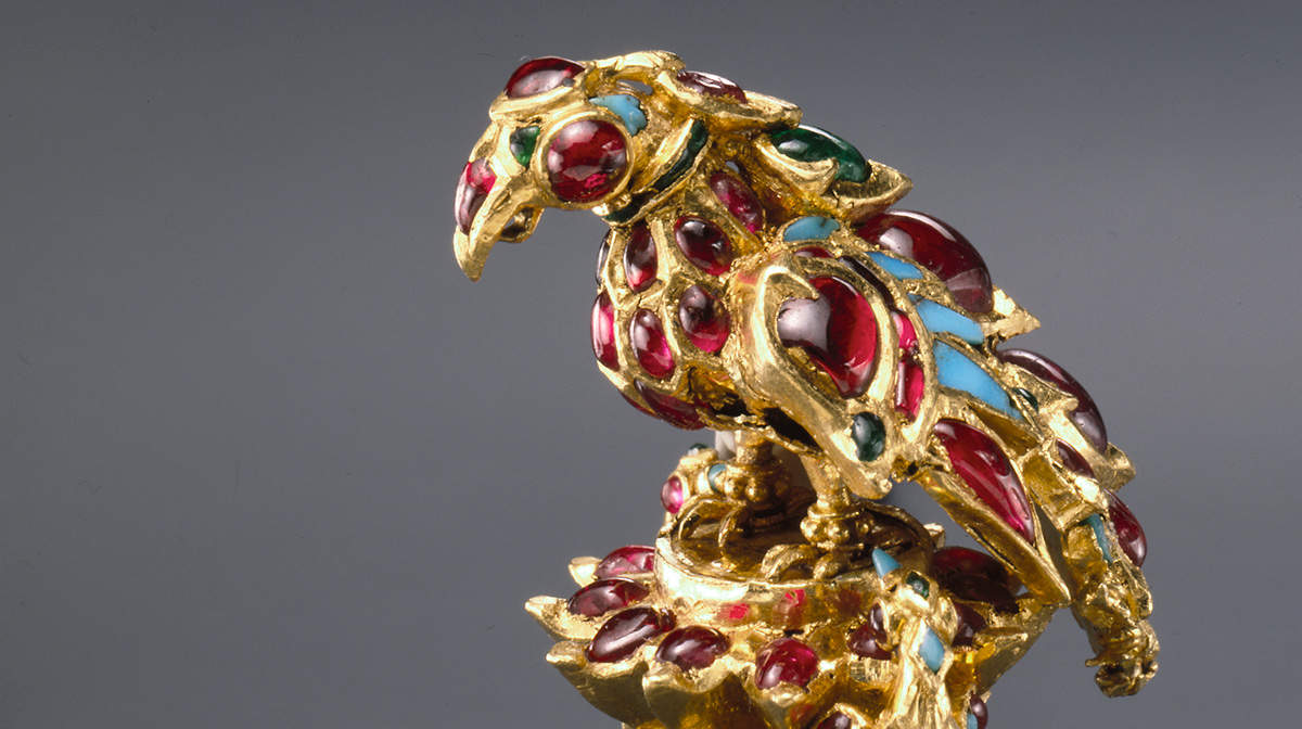 A ring with a bird of prey on top from the al-Sabah Collection. The ring is 17th century gold and covered with blue and red encrusted jewels including rubies, emeralds, and turquoise.