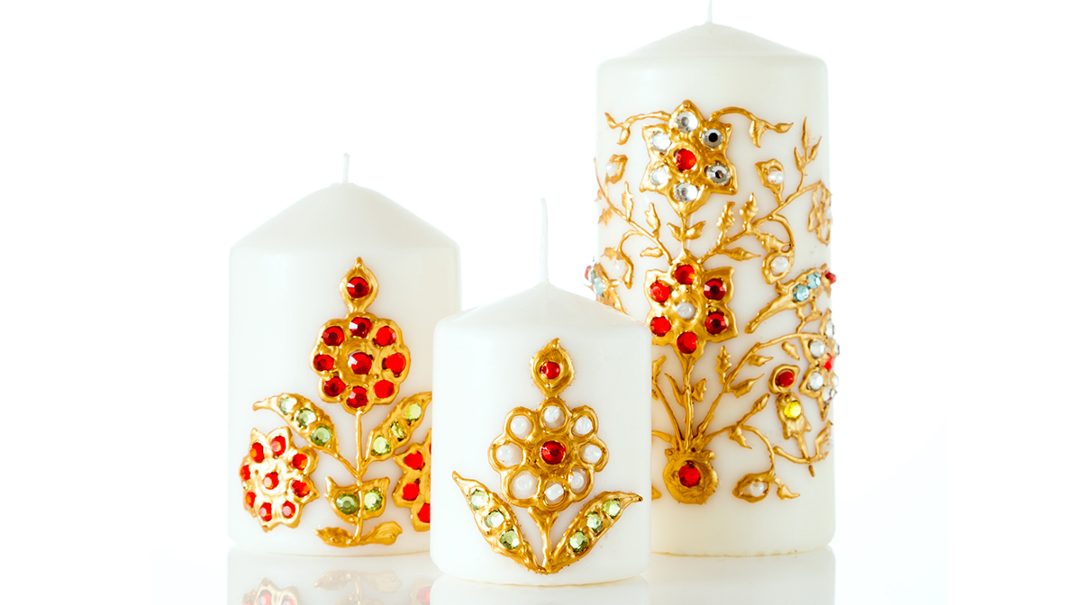 Three white candles of different sizes, each draped with gold flower trimming and decorated with red, silver, and green jewels