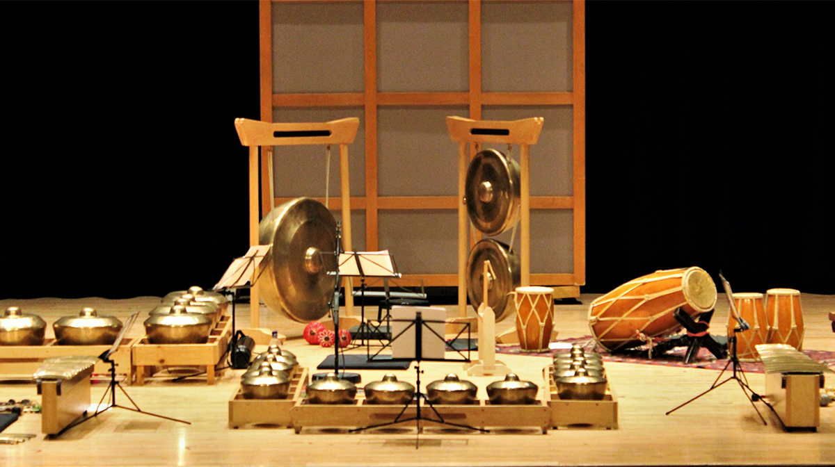 A collection of bronze instruments are displayed on a stage including flutes, gongs, and drums