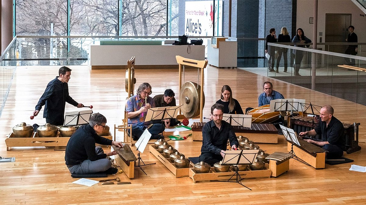 Sitting in a bright atrium, a group of musicians plays bronze instruments including flutes, gongs, and drums