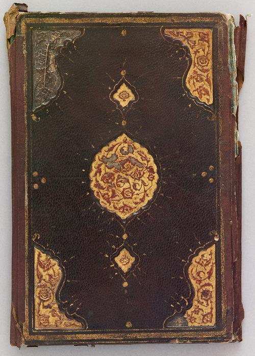 Back outer cover of dark-brown Turkish book binding with a gilt-stamped gold border and a centre gold and red medallion. Similar corner motifs as Centre medallion.
