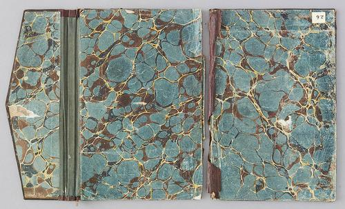 Inside, doublure of Turkish book binding with flap, laid open flat. Inner cover is a teal, brown and gold marbling. Spine between covers is ripped, and the spine of the flap is green.