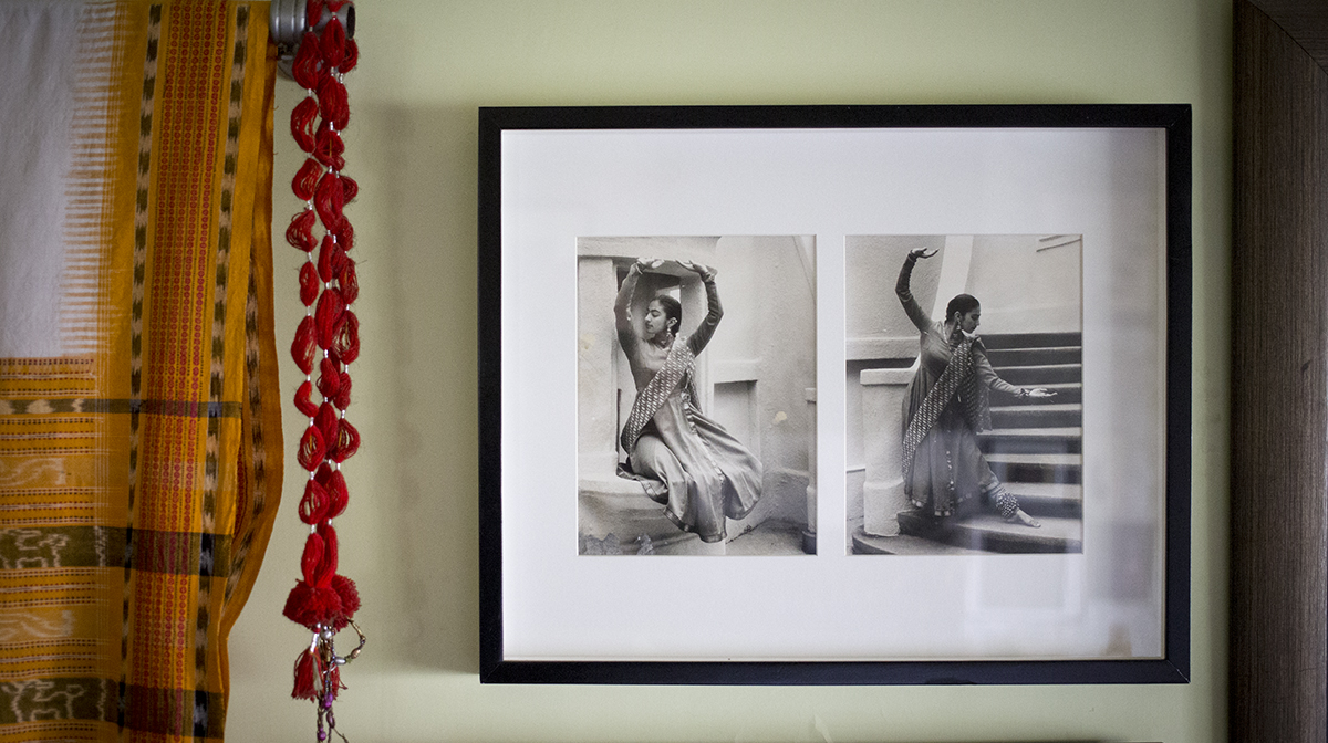 Family photos hanging a wall in which a female dancer holds several poses