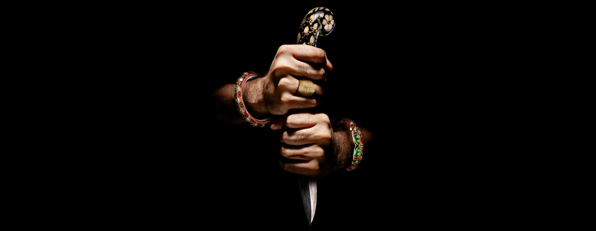 Two hands decorated in colourful jewellery emerging from darkness. The hands are tightly gripped around an opulent dagger.