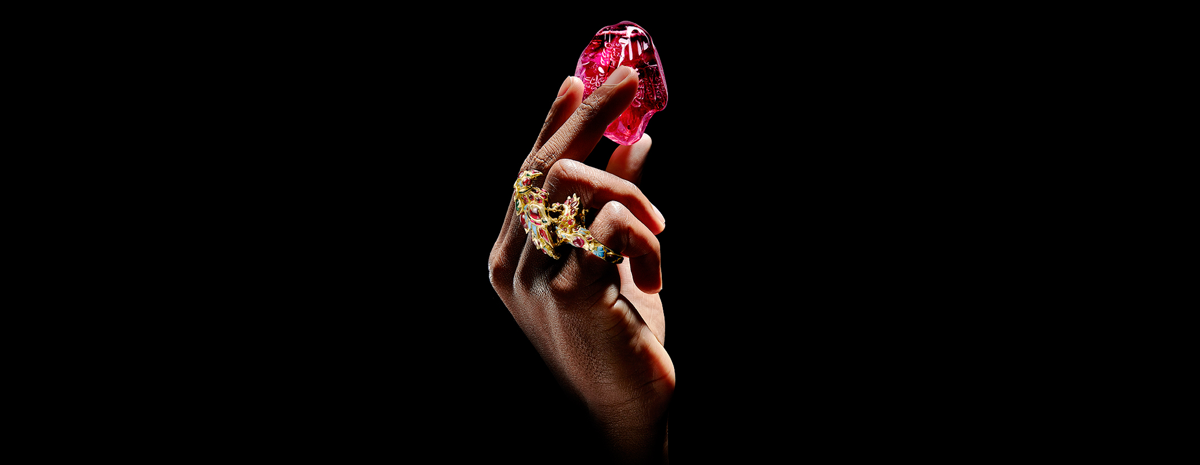 One hand emerges from the bottom of the photo wearing a golden bird-shaped ring covered in blue, red, and green jewels. The hand is delicately hoisting up and ruby stone with subtle carvings throughout it.