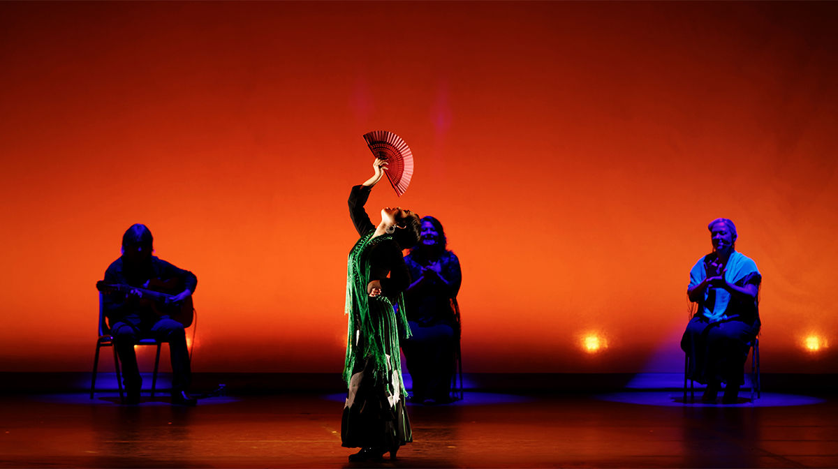 A woman in a green dress holds a flamenco fan above her. The stage is lit deep orange. Behind her three people sit clapping.