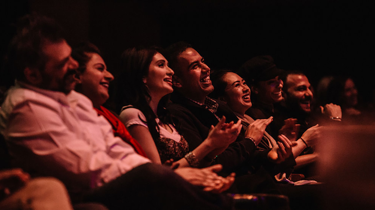 Eight people sitting in a row of the Museum's auditorium clap and smile.