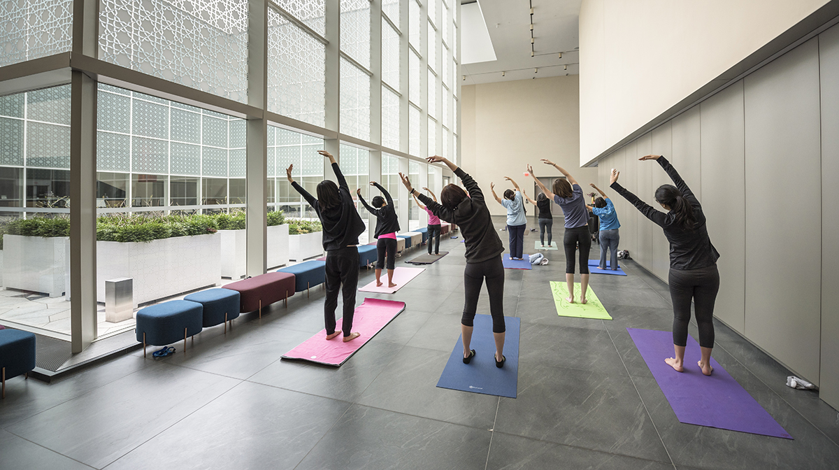 A group of women, facing away, lean to the left with arms raised during a yoga class in the Museum's atrium.