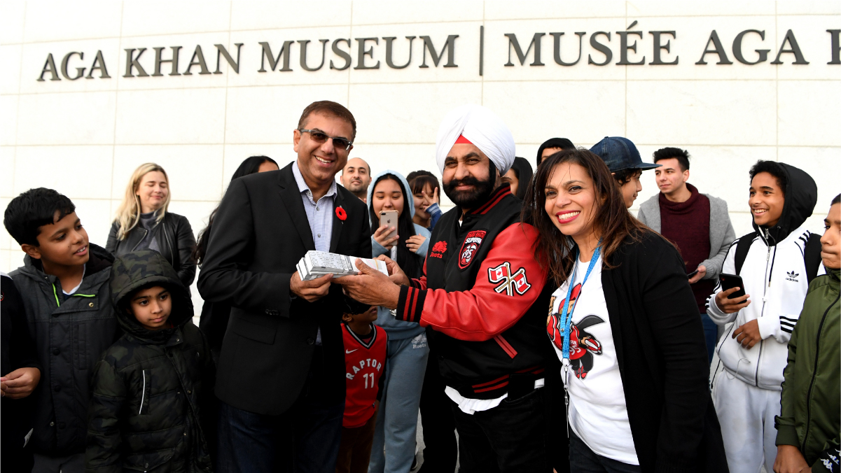 Museum CEO Moyez Jadavji accepts a bundle of tickets from Nav Bhatia, outside the Museum, surrounded by children.