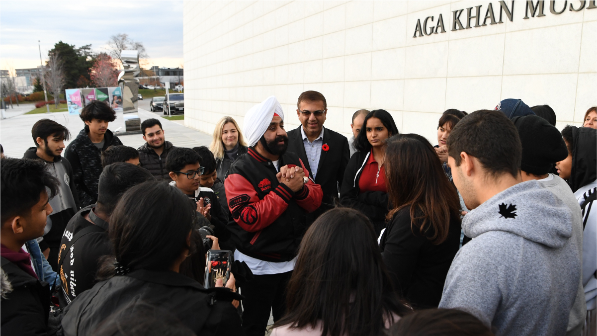 Outside the Museum, Nav Bhattia addresses a crowd of kids and Museum staff with his hands clasped.