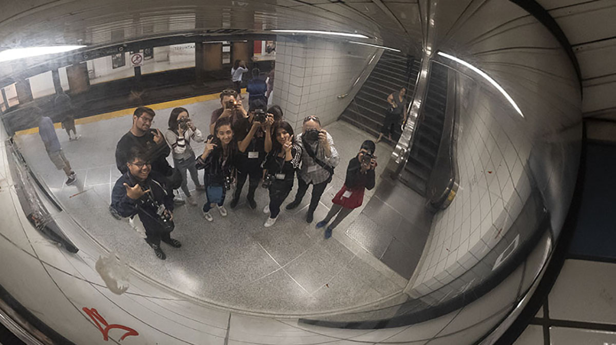 A line of student photographers standing on the subway platform looking up at a reflection of themselves in a mirror.