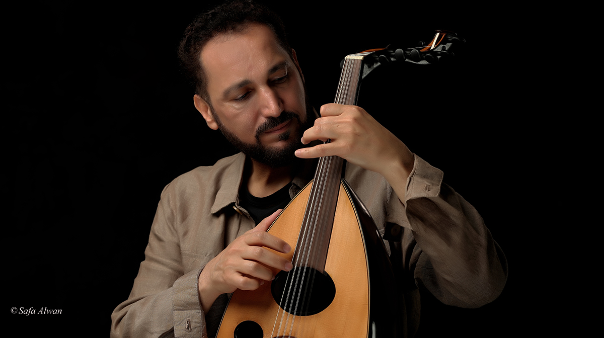 Naseer Shamma plays the oud against a black backdrop.