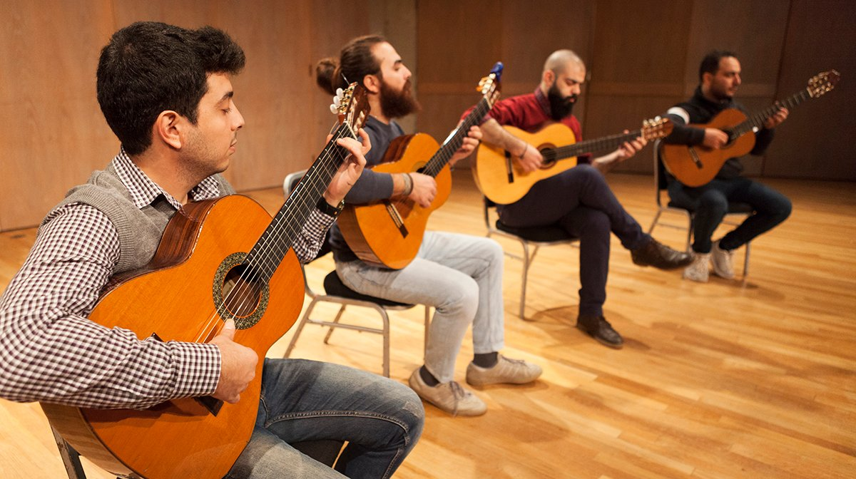 The four male guitarists in Orentes sit on chairs, playing the guitar on a stage with wooden floors.