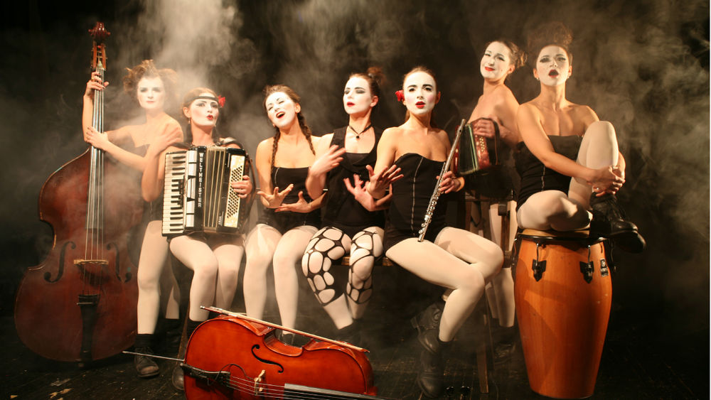 The seven members of Dakh Daughters stand on a smoky stage, wearing white face paint, surrounded by instruments.