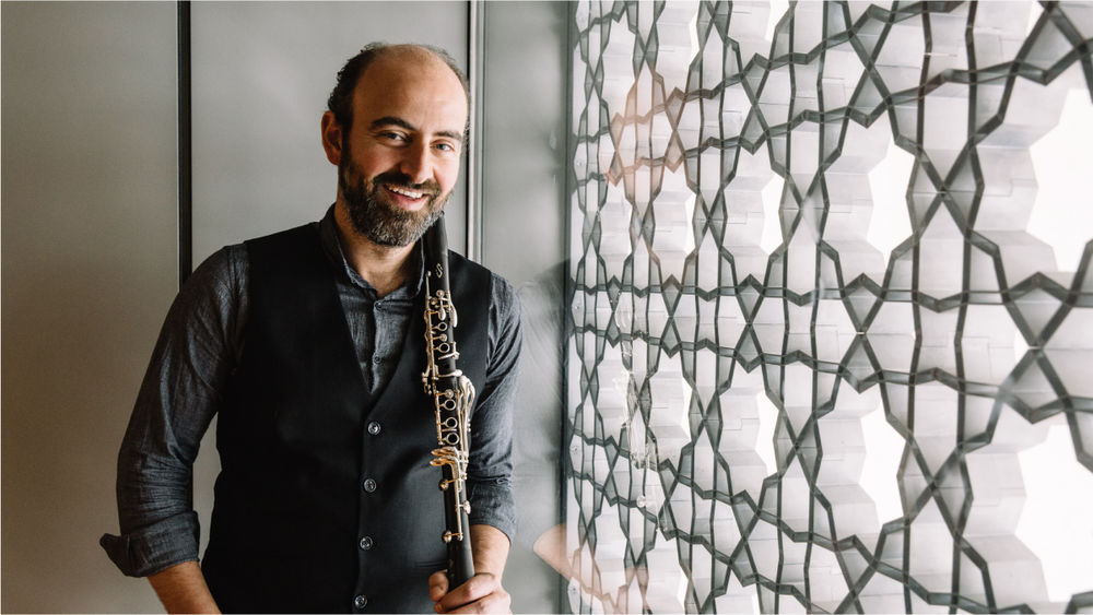 Kinan Azmeh, smiling and holding a clarinet against his shoulder, stands beside an intricate latticework screen at the Museum.
