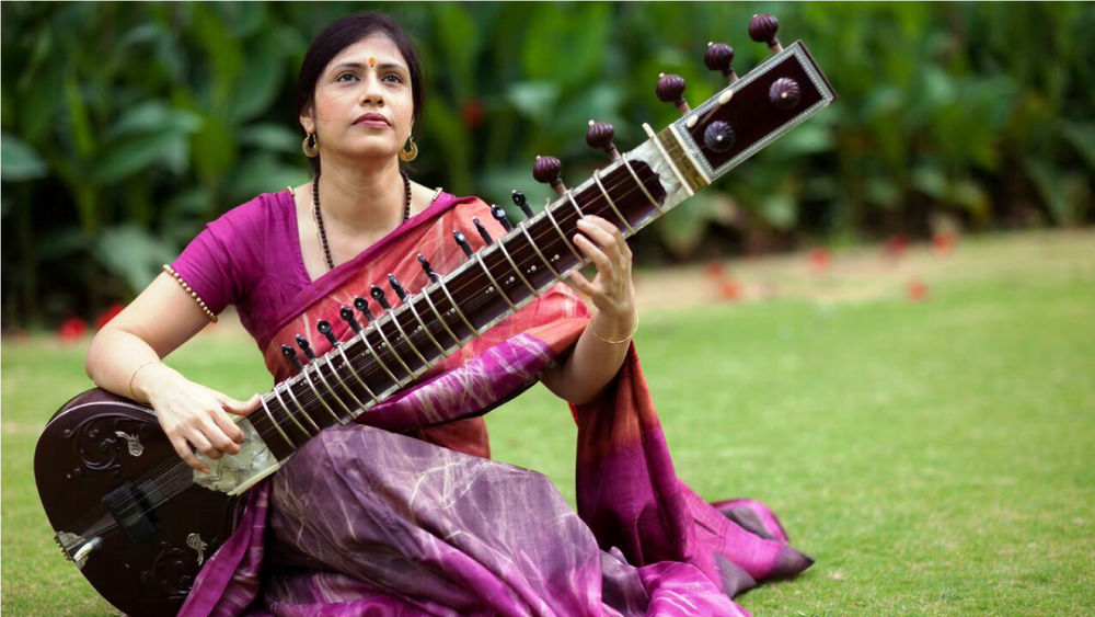 Vidushi Anupama Bhagwat sits on grass outside, wearing a plum-coloured sari, playing the sitar.