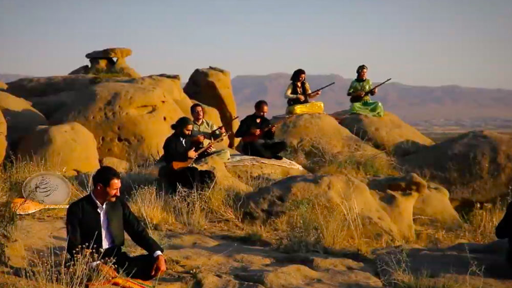 Four male musicians and two female musicians sit on rock formations, playing instruments in the setting sun.