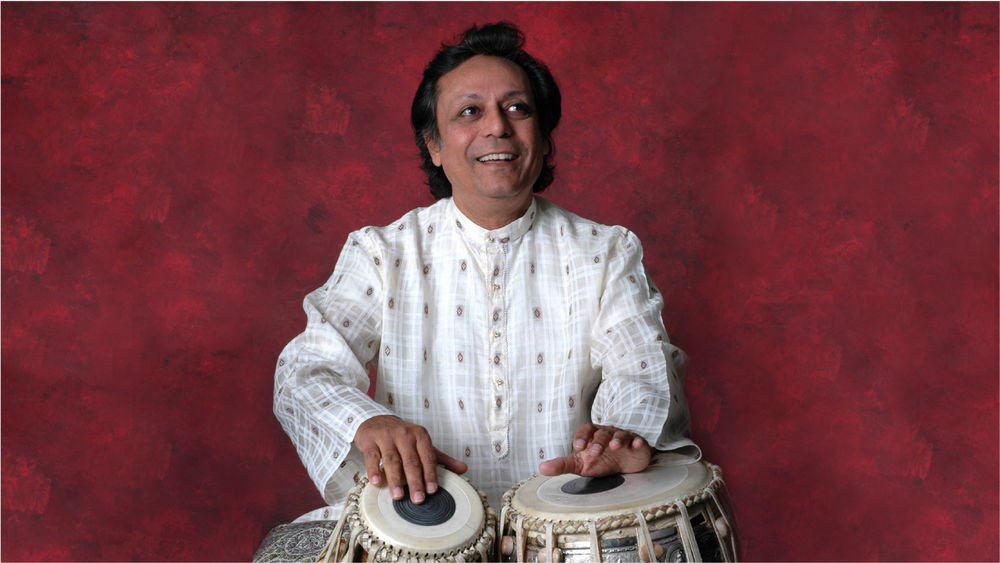 Swapan Chaudhari, wearing white, smiles and plays the tabla against a wine-coloured backdrop.