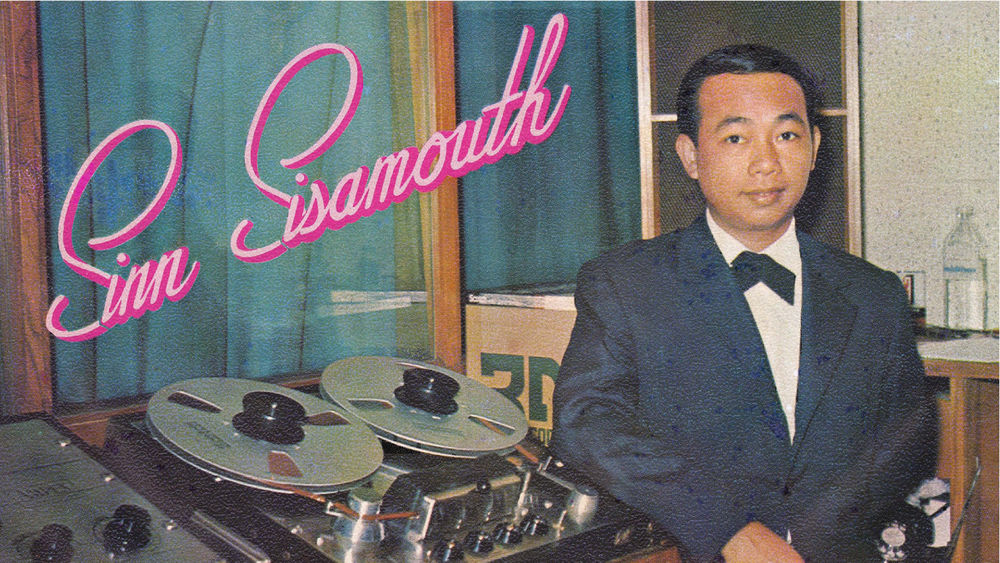 A male musician wearing a tux stands beside recording equipment with the words Sinn Sisamouth written in pink cursive on the top left.