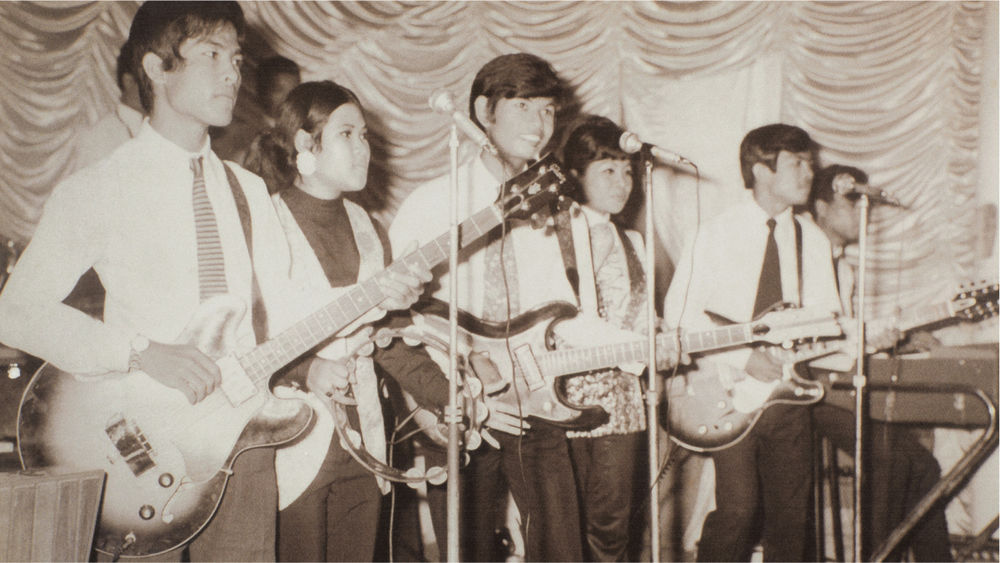 A black and white image of six male and female musicians performing on stage.