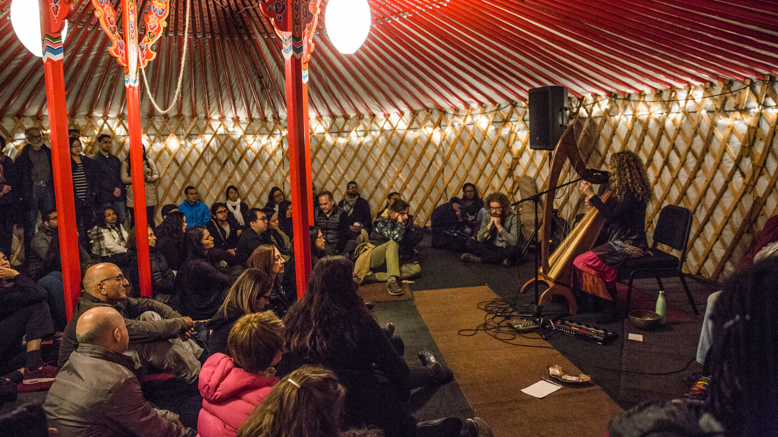 Spectators sitting on the floor enjoy the music of a harp player inside a Mongolian yurt.