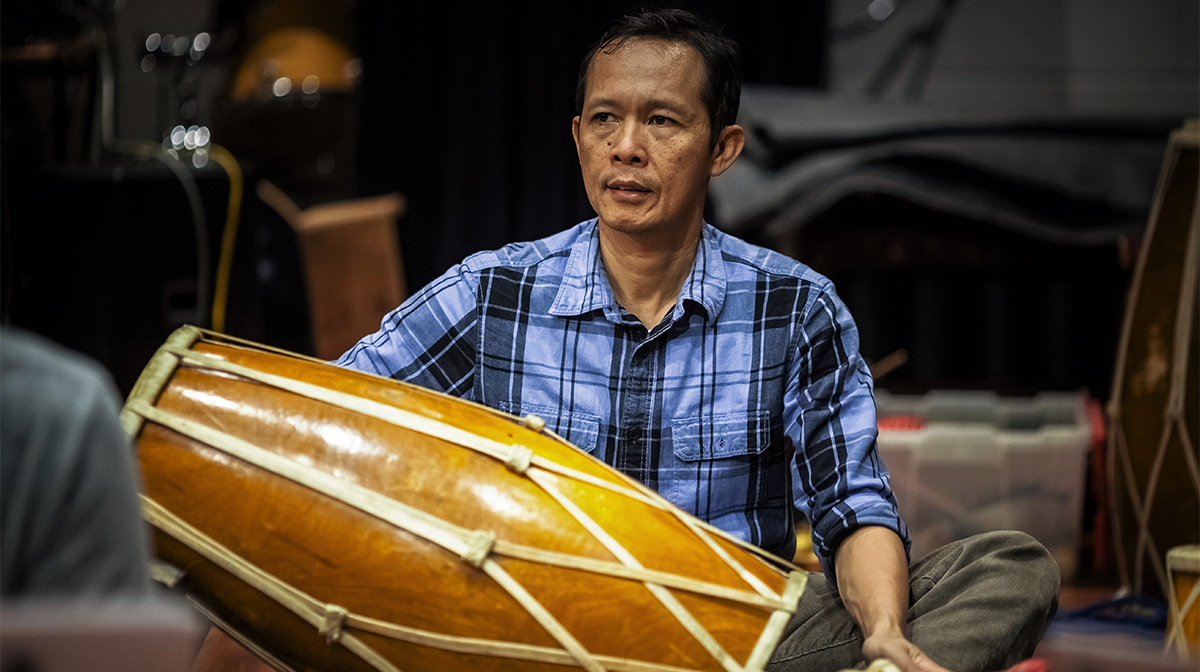 A man in a blue-and-black check shirt sits holding a large two-headed hand drum