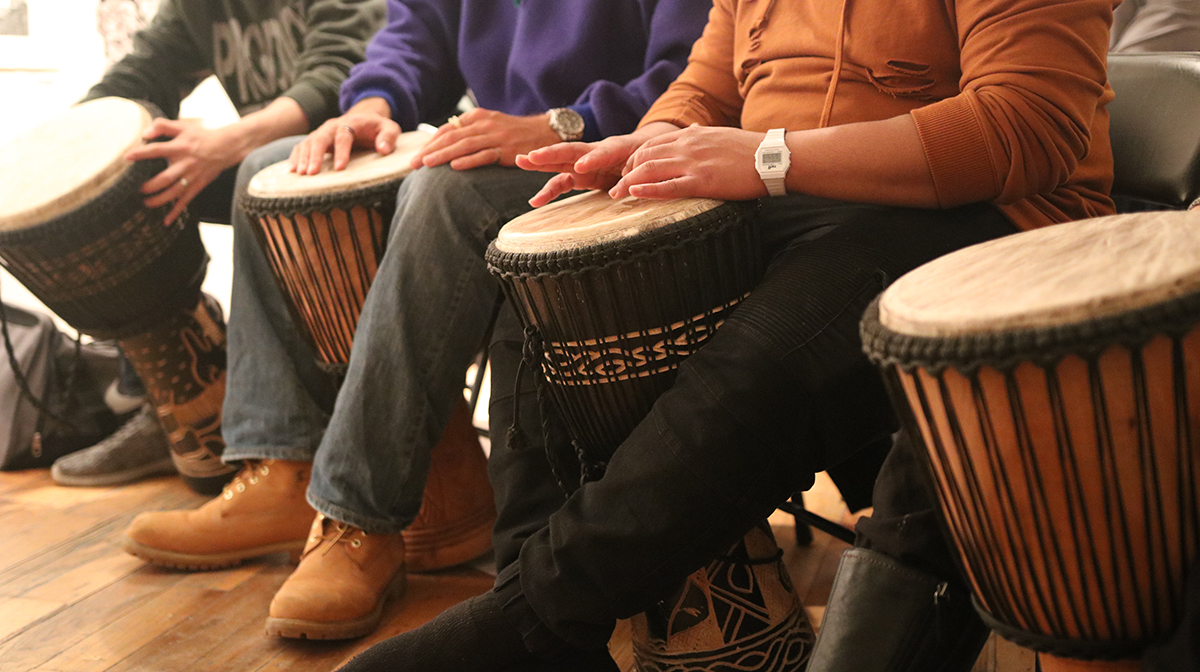 The hands of three men on djembe drums.