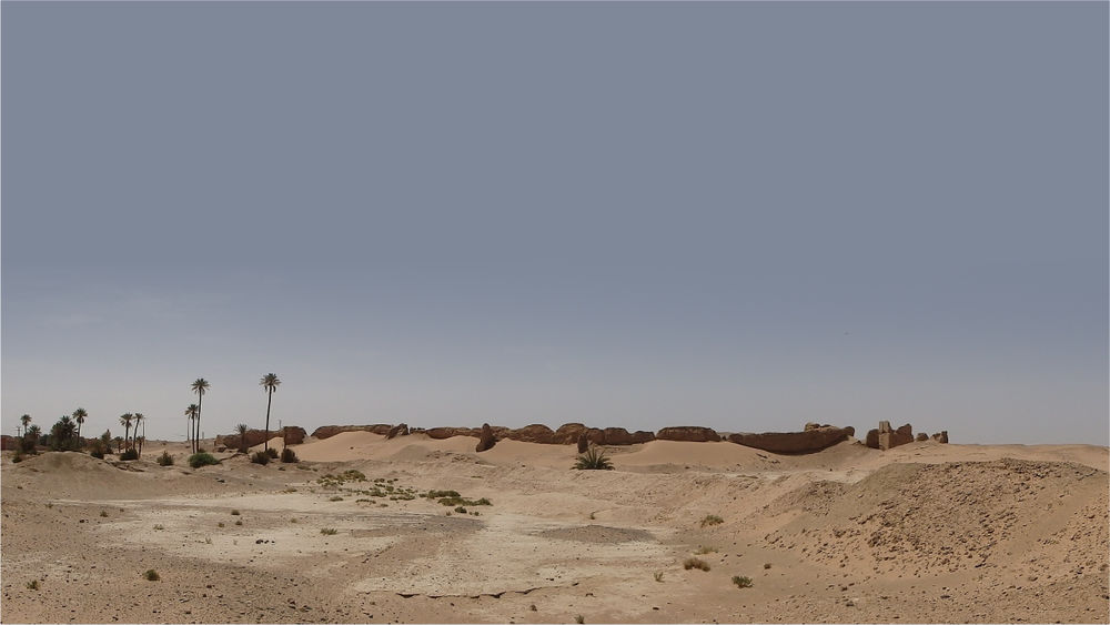 A desert landscape with sand dunes in the foreground and a line of ruined walls on the horizon.