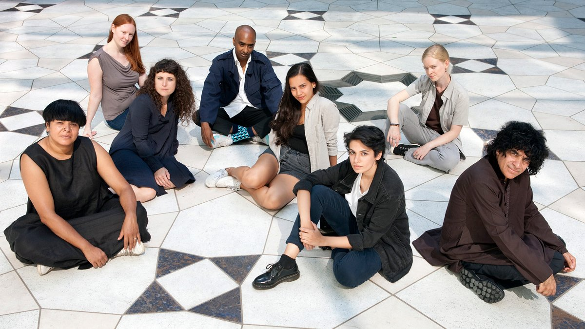 A group of eight young women and men pose seated on the tiled, geometric-patterned floor of the Museum's courtyard during the day.