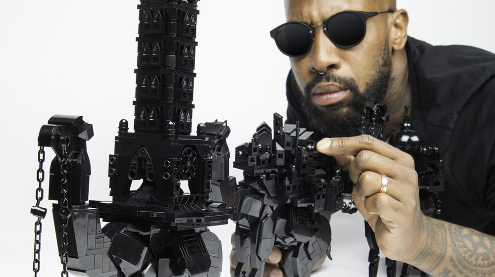 A man in sunglasses crouches down to touch a camel sculpture made of shiny black Lego pieces.