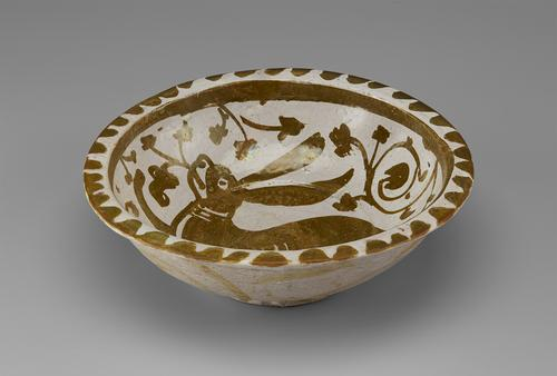View of a circular bowl, decorated in softly metallic gold paint over an off-white base. The flattened rim is decorated in a scalloped pattern, with a large, floppy-eared hare surrounded by flowers in the centre. The outside is decorated with soft daubs of paint.