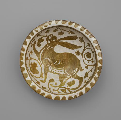 Top view of a circular bowl, decorated in softly metallic gold paint over an off-white base. The rim is decorated with a scalloped pattern, while in the centre is a large, floppy-eared hare surrounded by flowers.