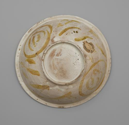 "Bottom view of a circular bowl, showing a slightly raised base and a flattened rim. The bowl is painted off-white, with circular lines and daubs of soft golden paint. There is an oval paper sticker on one edge that reads ""H. Kevorkian Collection"" with ""2672"" written on it in pencil."