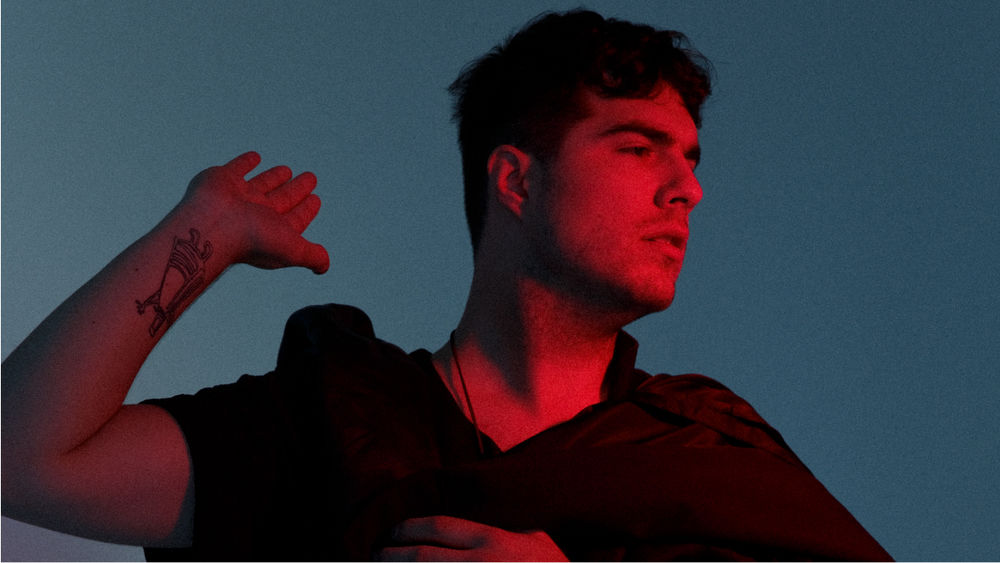 Jeremy Dutcher stands against a blue backdrop in an orange glow, wearing a brown cape and holding up his right hand.