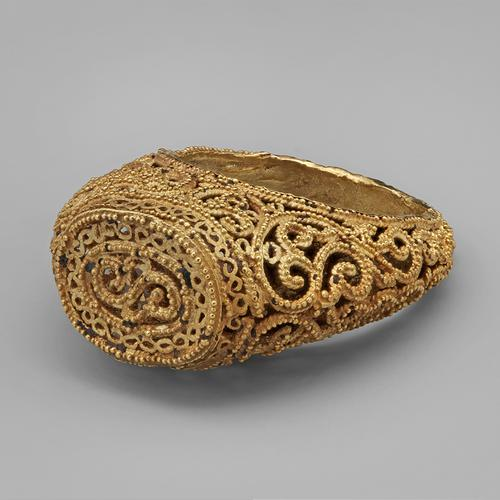 Golden ring laying on its side, view of the top oval bezel and flat top, featuring filigree and granulation, with arabesques widening towards the bottom of the band.