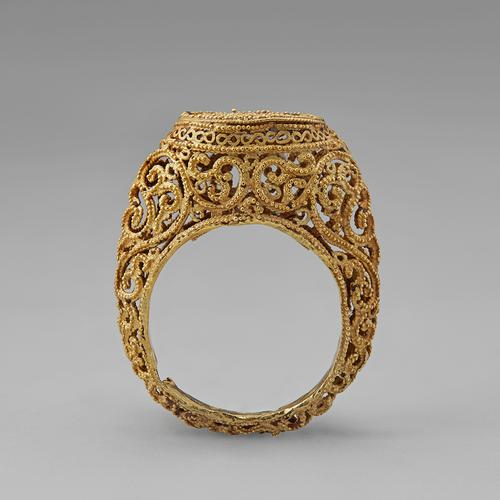 Side view of the golden ring standing straight up on its band. Side view of the filigree and granulation that create this ring.