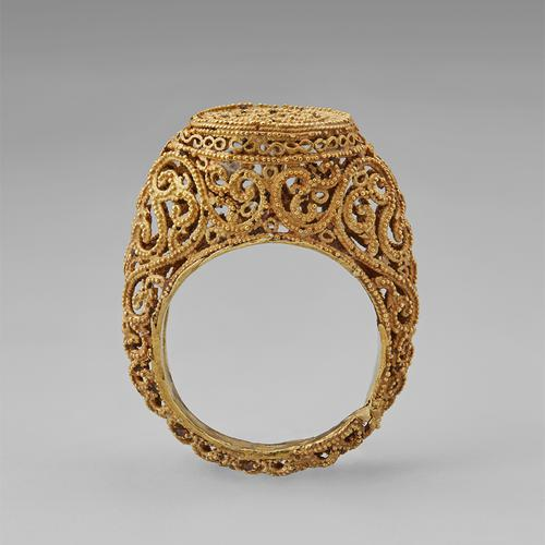 Opposite side view of the golden ring standing straight up on its band. Side view of the filigree and granulation that create this ring.