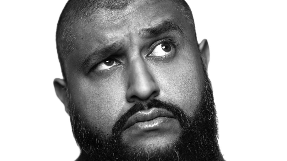 Comedian Azhar Usman's looks up to the corner with a serious expression in a black and white headshot.
