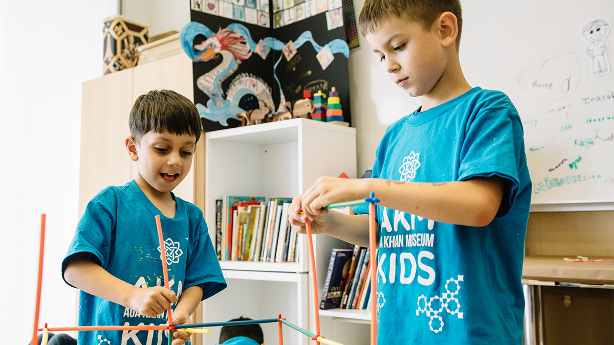 Two boys wearing Aga Khan Museum Summer Camp t-shirts build a colourful plastic structure in a classroom.