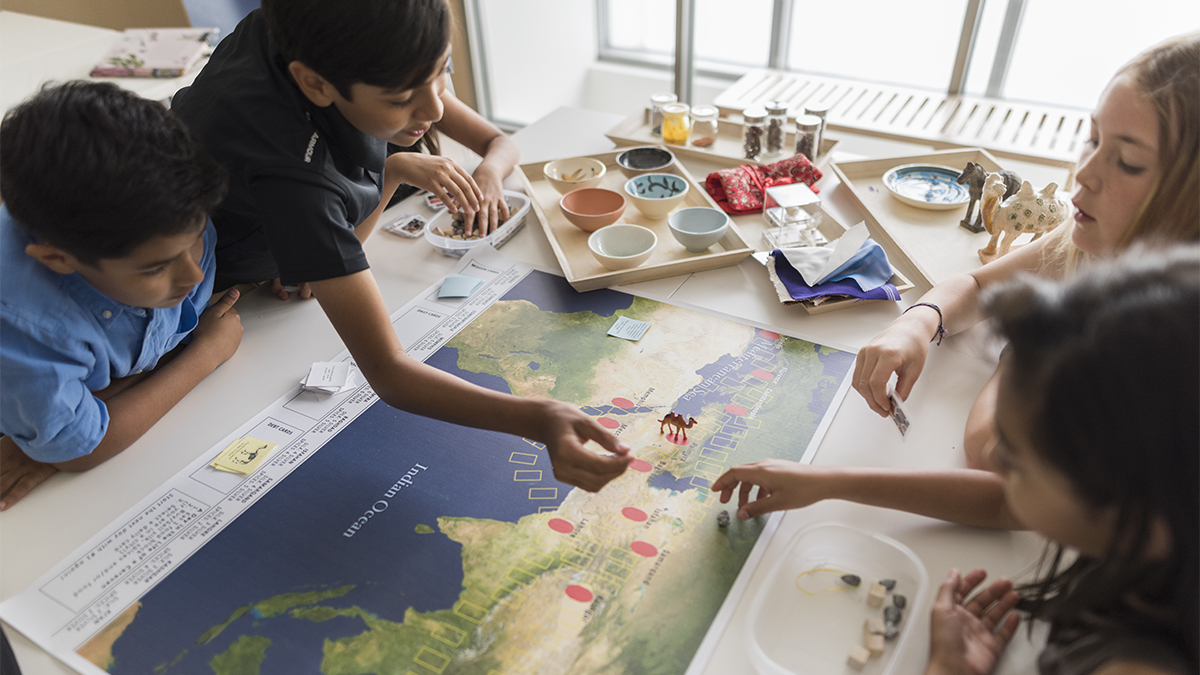 Four kids at a table play a game on a board showing the geography of South Asia and the Middle East.