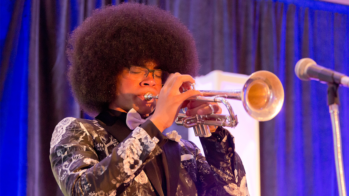 William Franklyn Leathers plays the trumpet with eyes closed on stage in front of a microphone.