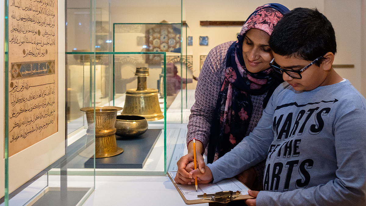 A woman helps guide the hand of a boy who is sketching in front of a folio in the Museum's permanent gallery.