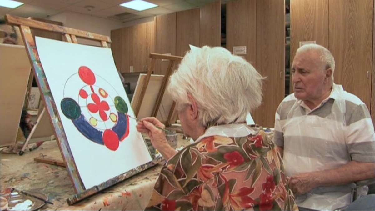 Inside a studio, an elderly woman works on a circular painting, as an elderly man looks on.