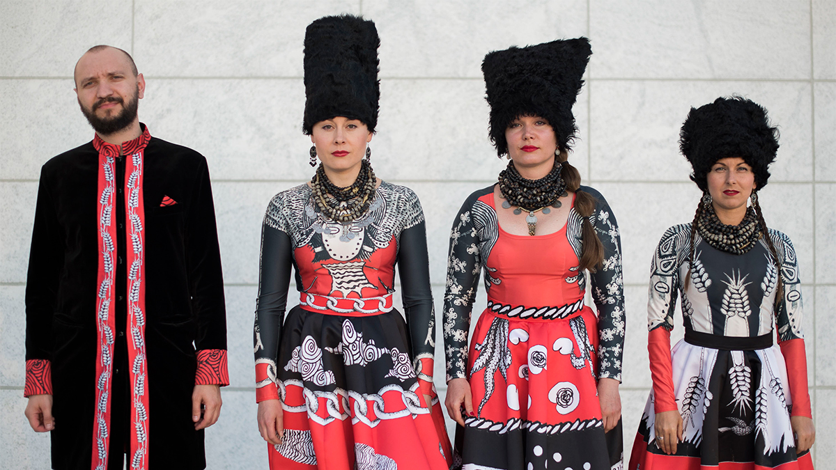DakhaBrakha's four members stand outside the Museum, wearing red, black, and white outfits, and tall, woolly black hats.