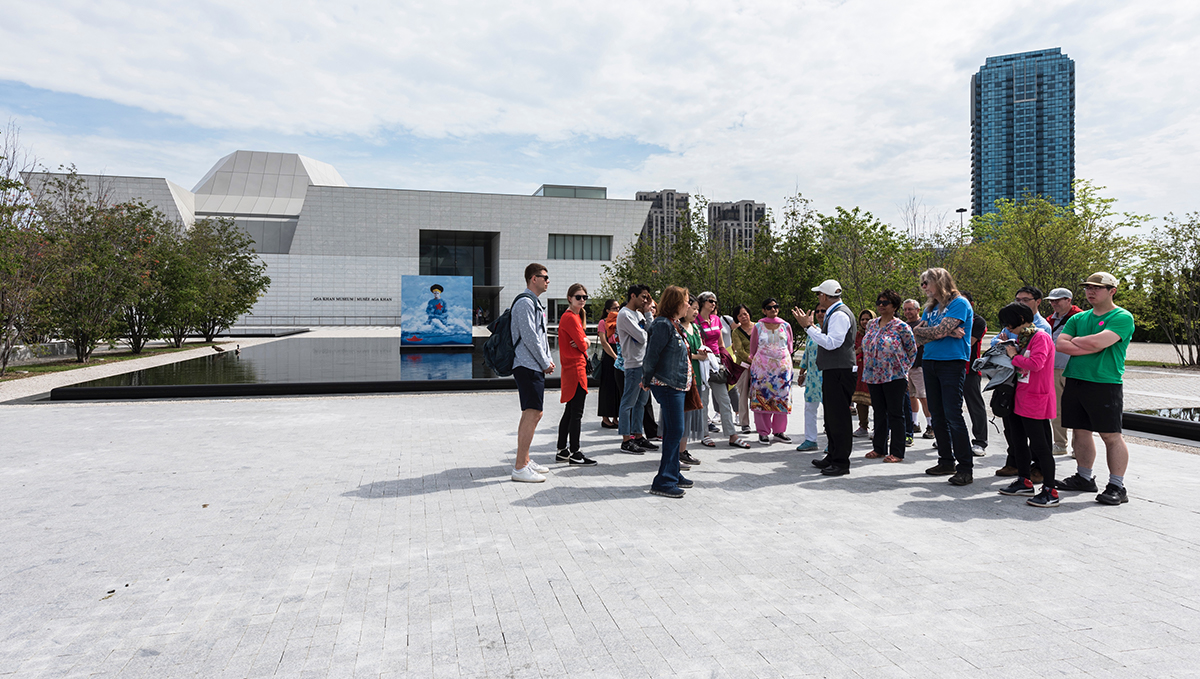 A volunteer leads a group of about 20 people on a tour of the Aga Khan Park at the Aga Khan Museum in Toronto.