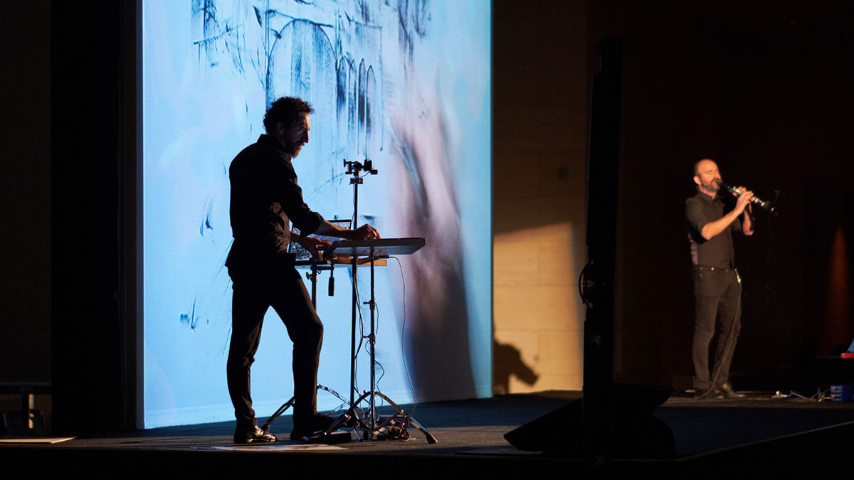 On stage, an artist draws at a table as the image appears on a large screen, while a clarinetist plays on the side.