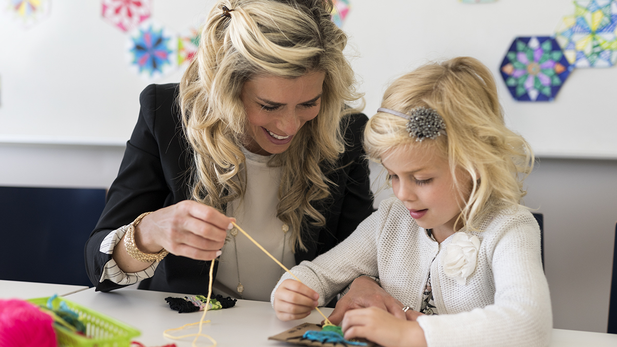 A young girl enjoys arts and crafts activities with her mother