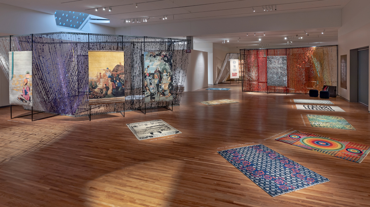 About six four-by-six foot carpets with unique designs lie on wood-panel floor of the Aga Khan Museum's temporary exhibitions gallery.