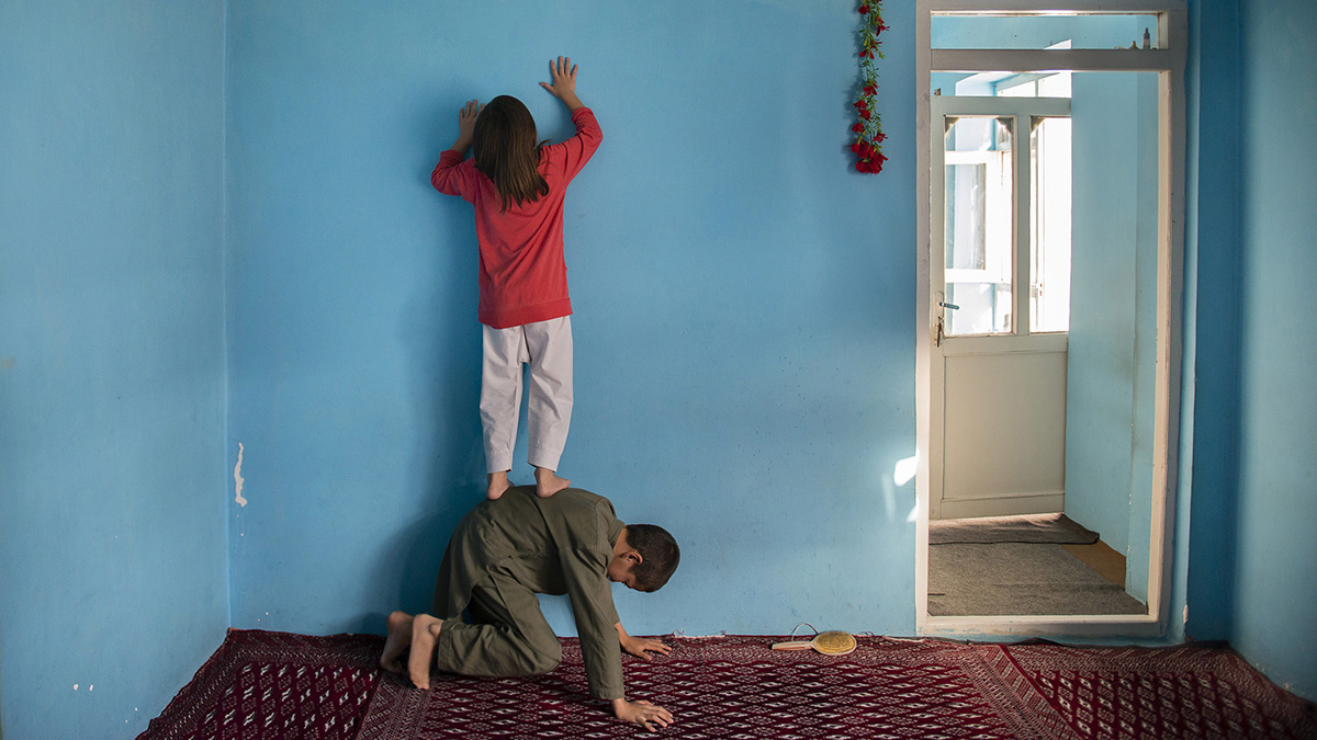 A girl stands on her brother's back to hang a photo of their father on the wall.